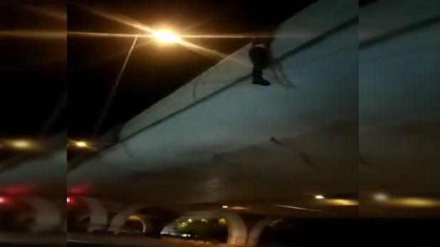 Young man climbing on flyover to commit suicide, पत्नी से झगड़े के बाद आत्महत्या करने फ्लाइओवर पर चढ़ा युवक, रेलिंग से लटका, वीडियो वायरल